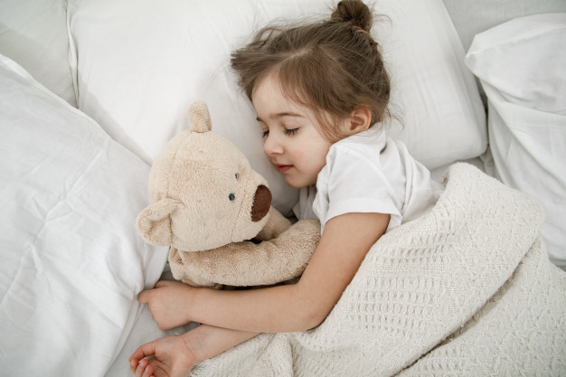cute-little-girl-is-sleeping-bed-with-teddy-bear-toy_169016-4225