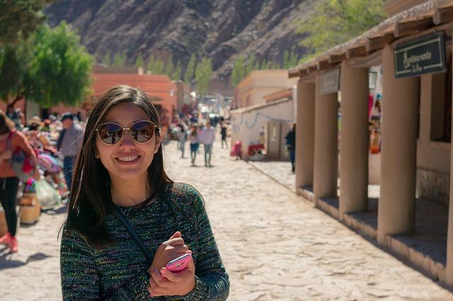 Žena v slnečných okuliaroch stojí na ulici a usmieva sa.jpg