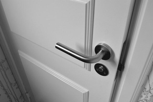 Detail na biele zatvorené dvere so striebornou kľučkou
