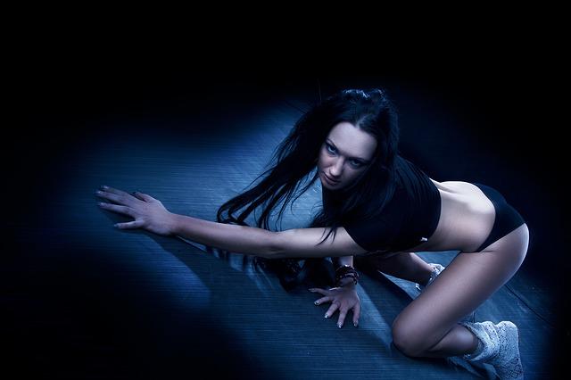 Žena s dlhými vlasmi kľačí na zemi v sexy póze