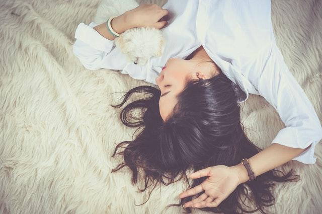 Žena s malým bielym psom na posteli